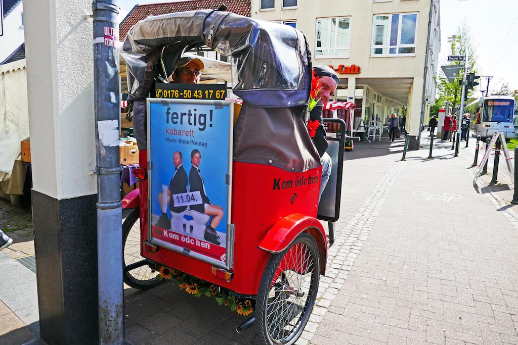 """Nicht nur umweltfreundlicher Fahrspaß, per Rikscha rührt das Kom(m)ödchen auch gleich die Werbetrommel für das neue Programm """"fertig"""" von Martin Maier-Bode und Jens Neutag"""