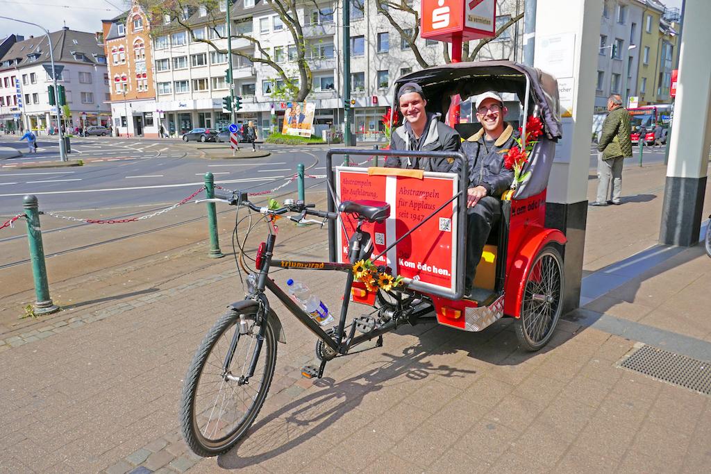 Rikscha-Pilot Tobi (re) steht mit Kumpel Markus in der Kom(m)ödchen-Rikscha am Gerresheimer Markt. Kundschaft willkommen…   Fotos: LOKALBÜRO